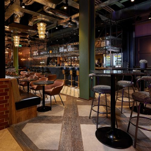 Runyon's Bar - Tables at wheelchair height mixed with high tables & bar stools. Flooring is flat & smooth & patterned contrast to main walkway. Lower bar area at wheelchair height for orders. Well lit & high ceilings. Can be noisy when full.