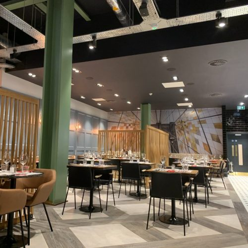Runyon's Restaurant - Well Lit with industrial style high ceiling for good acoustics. Flooring flat & smooth with pattern for colour contrast with main walkway. Ground Floor disabled toilet opposite main walkway. Tables wheelchair height, no leg obstruction.