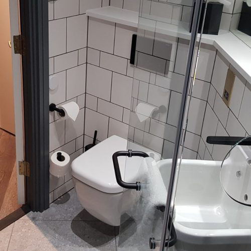 "Liberty Ambulant Access Room - WC - 3""/5cm step into bathroom. Smooth non slip floor. Toilet 48cm high. No grab rails at WC. Grey Tiled floor & white tiled wall. Sink near WC & at standing height. Glass shower door porthole accesses temp. controls prior to shower. Black grab rail on shower door. Black taps on white good colour contrast."